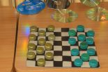 Sustainable draughts game made from piece of floor material and used bottle caps